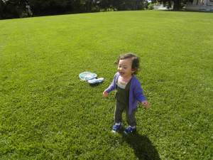 Running through the open grass while playing her hat game.